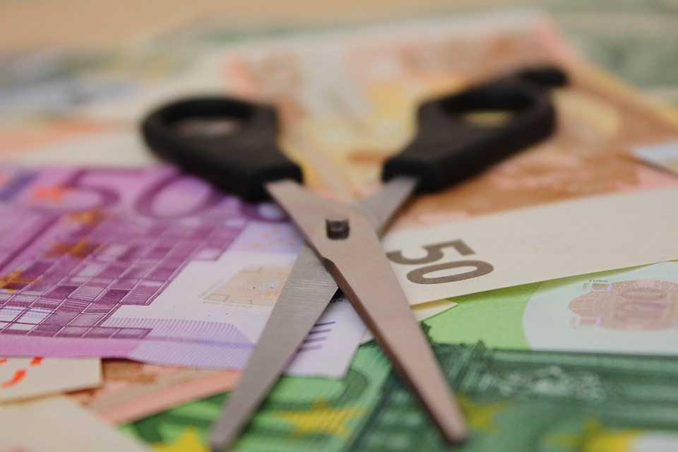 מס הכנסה - צילום של מספריים ושטרות