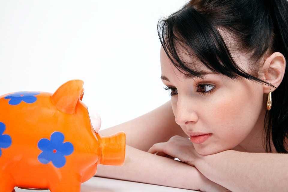 אישה עם קופת חיסכון למימון הפסיכומטרי